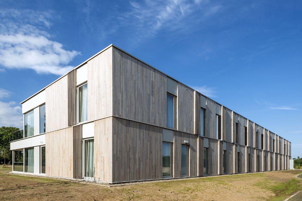 Dankzij de cederhouten gevelbekleding versmelt de nieuwbouw met de Haspengauwse natuur. (Foto: Marc Sourbron)