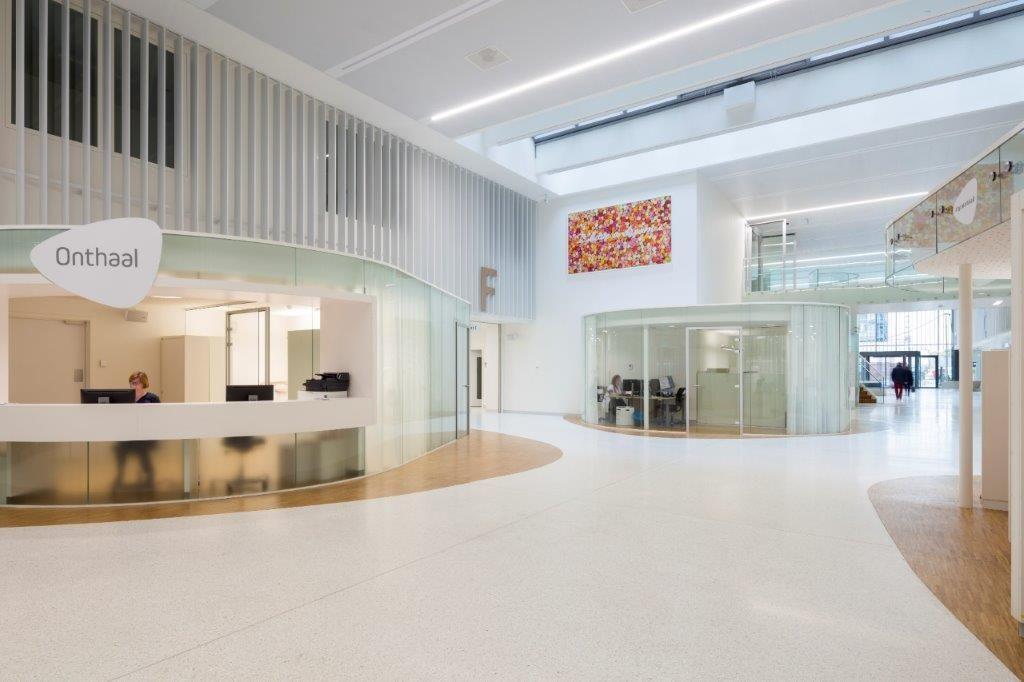 De hoge inkomhal is groot en helder, met dank aan imposante glasvlakken en het overwegend witte interieur. (Beeld: Ruimtesinbeeld)