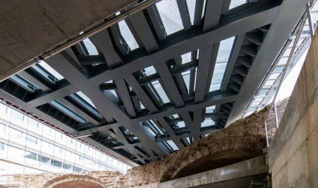 Aangezien de onderliggende archeologische resten zichtbaar moesten blijven, is de trambrug afgewerkt met roostervloeren.