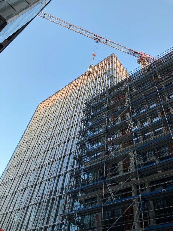 De aluminium raamkaders zijn grotendeels bedekt met een witte aluminium voorhangstructuur. Het subtiele samenspel tussen rechte en diagonale elementen creëert een dynamisch, licht golvend effect.
