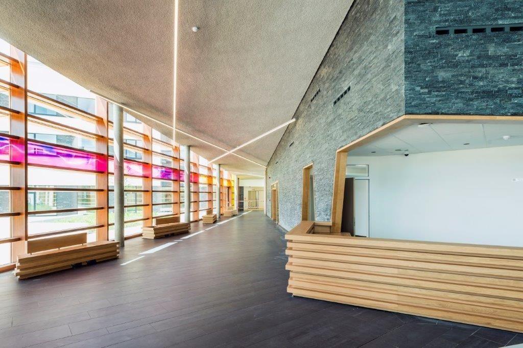 Accoyahout en leisteen markeren het fraaie onthaal. Een kleurrijk glaskunstwerk, dat horizontaal doorloopt over de volledig beglaasde gevel van het inkomgedeelte, verleent deze ruimte een sfeervol cachet. (Foto: Marc Sourbron)