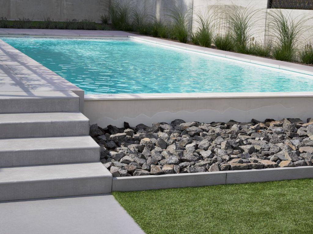 L'escalier sobre fait bien plus que combler une différence de niveau, il met la piscine en scène, il se fond avec le bord de la piscine et la bordure basse en pierre décorative pour former un grand ensemble qui élève votre jardin au rang d'espace de vie.