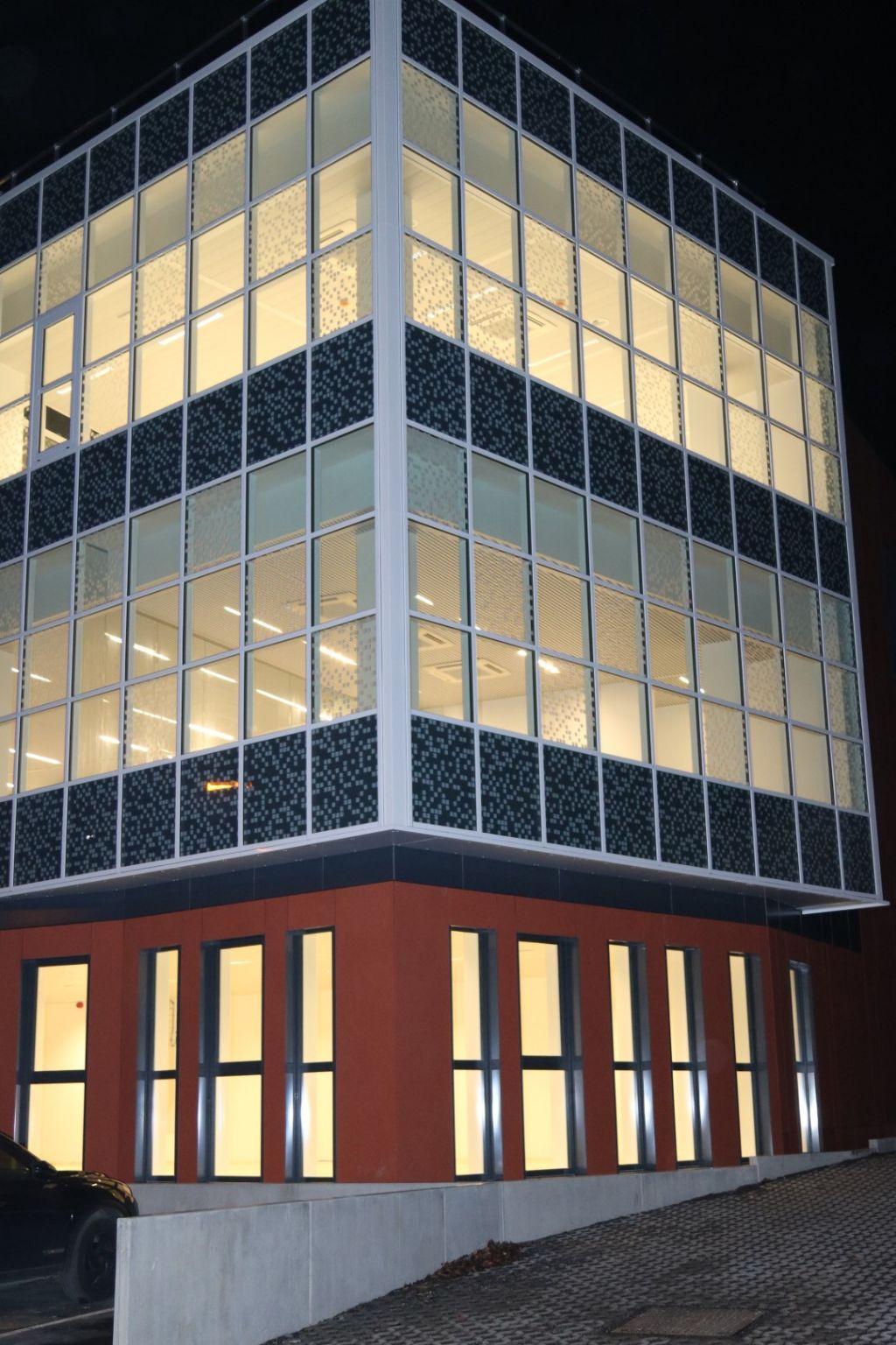 Vue nocturne du bâtiment et de sa façade vitrée.