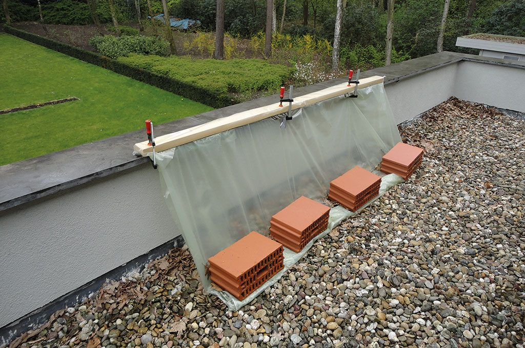 Het tijdelijk van slagregen afschermen van een gedeelte van de dakopstand.
