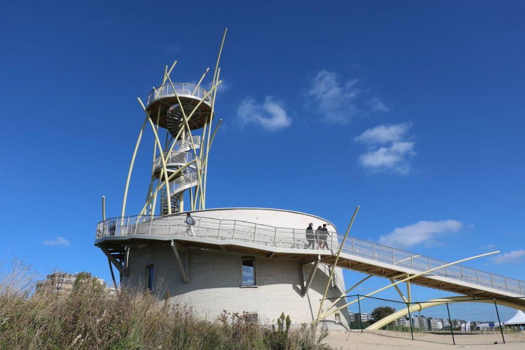 Een brug en helling rondom de bakstenen sokkel geeft toegang tot een eerste uitkijkplatform.  De impact van het toegangspad op de omgeving wordt zo beperkt mogelijk gehouden.