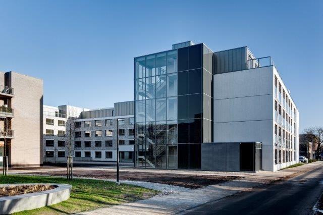 De grotendeels geprefabriceerde gevels zijn deels opgebouwd uit metselwerk en deels uit wit architectonisch beton.