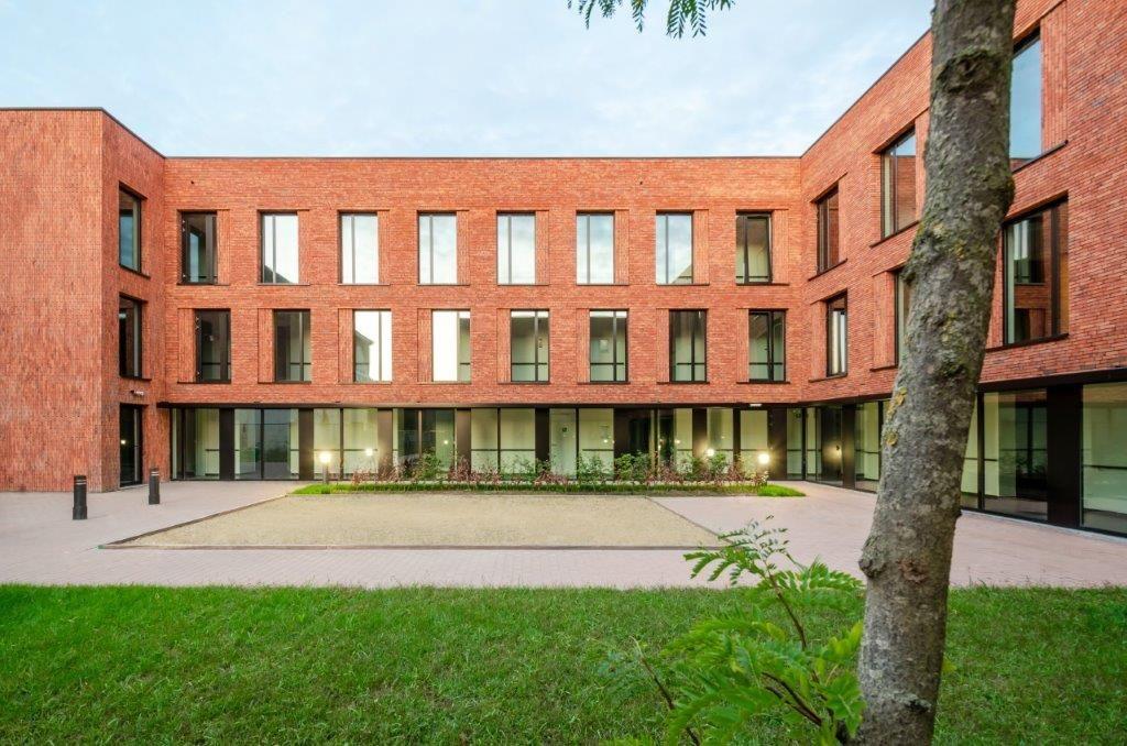 De combinatie van rood-oranje genuanceerde bakstenen, inpandige terrassen en verticaal gestapelde niveaus staat garant voor een massief gevelbeeld met een subtiele dynamiek.
