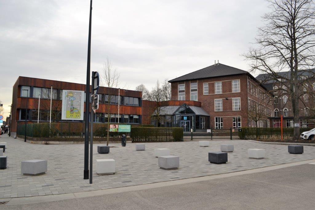 Zitelementen in architectonisch zelfverdichtend beton sieren het plein voor de basisschool.