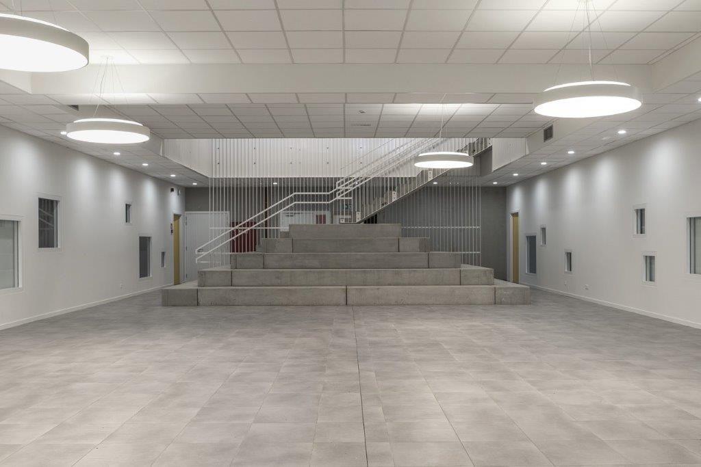 Het gelijkvloers en de eerste verdieping zijn met elkaar verbonden via een monumentale trappenpiramide in prefabbeton, die tegelijk fungeert als tribune en podium. (Beeld: Régine Mahaux)