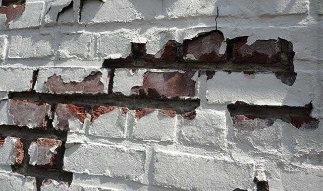 Voorbeeld van schade ten gevolge van vochtophoping in de baksteen: loskomen van de verf en vorstschade ter hoogte van de voegen en de baksteen.