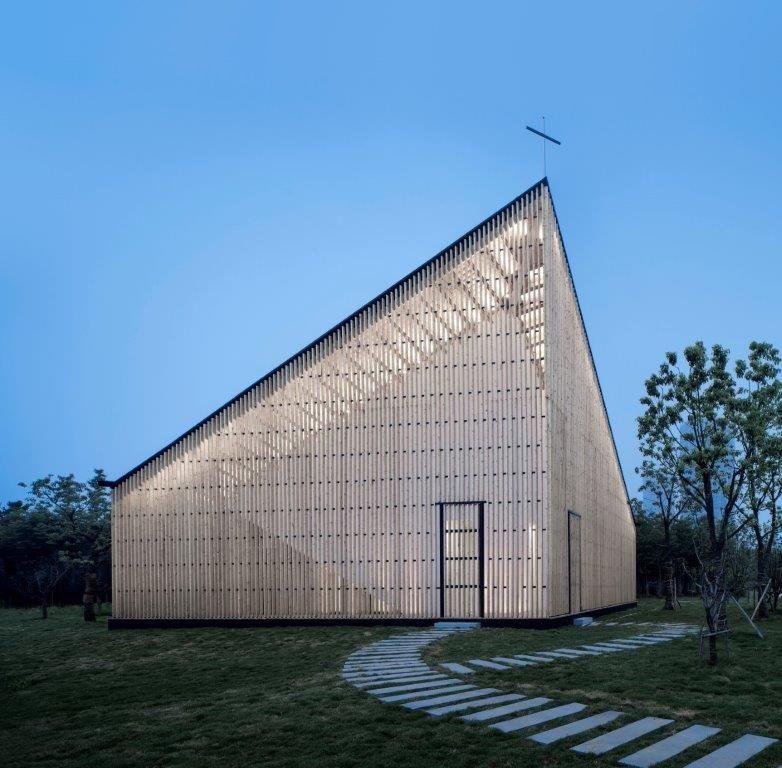 Een van de meest opvallende kenmerken van het overwegend houten gebouw is het atypische profiel: een variatie op het typische vlinderdak, dat in twee hoeken van het vierkante grondplan aan hoogte wint. (Foto: Yao Li)