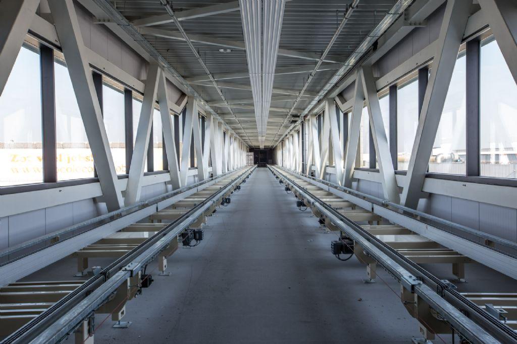 Automatische transportbanen in de transportbrug vervoeren zowel palletten met afgewerkte producten (naar het magazijn) als grondstoffen (naar de productiehal).