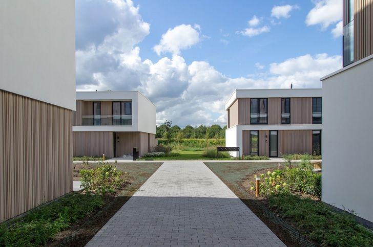Een doorsteek tussen de twee appartementsblokken aan de straatzijde leidt naar de achterliggende eengezinswoningen en het bufferbosgebied.