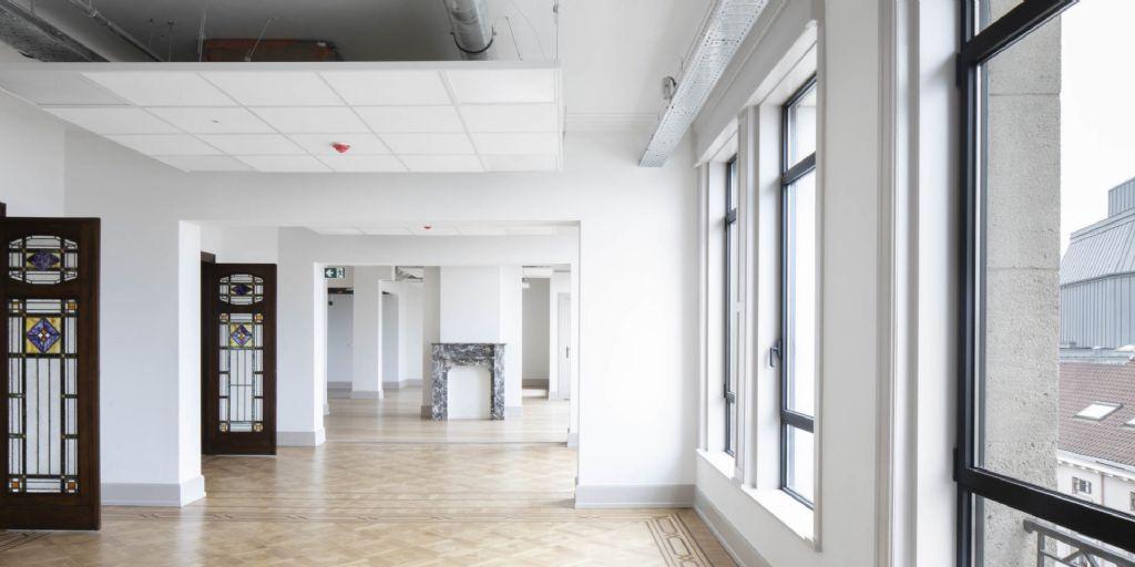 Une combinaison de cheminées en marbre, de faux-plafonds et de techniques (câbles et tuyauteries) visibles, un bon résumé du travail de rénovation effectué.