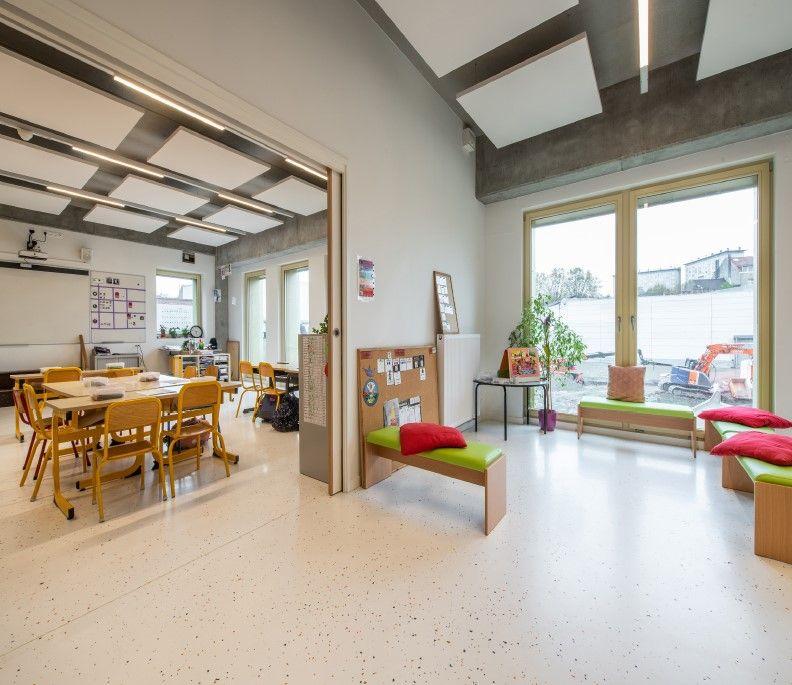 Un sol lisse et clair agrandit l'espace dans une nouvelle école primaire