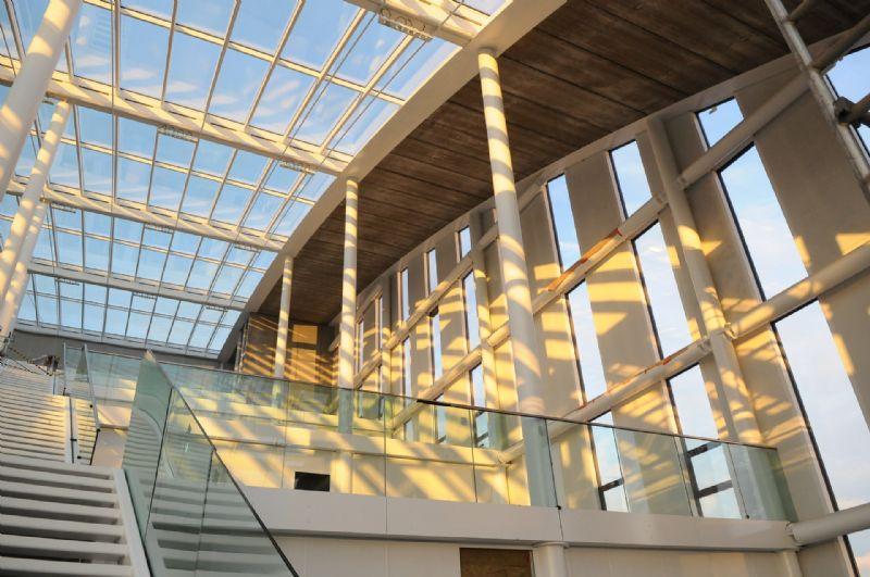 Bezoekers komen bij het betreden van het gebouw terecht in een imposant atrium dat baadt in het invallend daglicht.