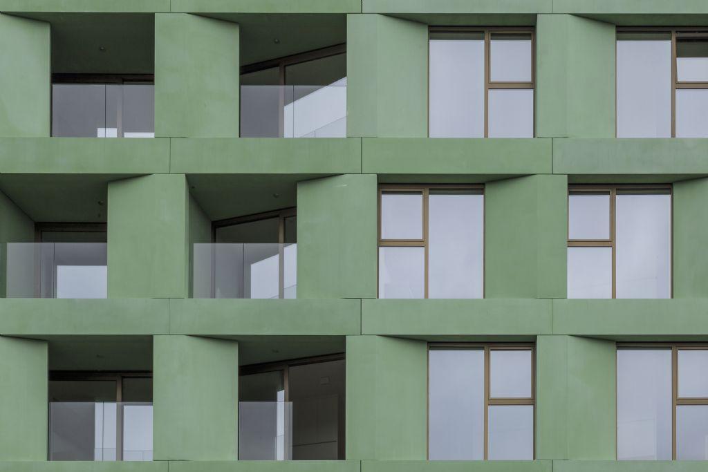 Alle zichtbare gevelelementen van het Woods-gebouw zijn uitgevoerd in groen gezuurd beton, van panelen over dorpels tot druiplijsten. (Beeld: Crepain Binst Architecture)