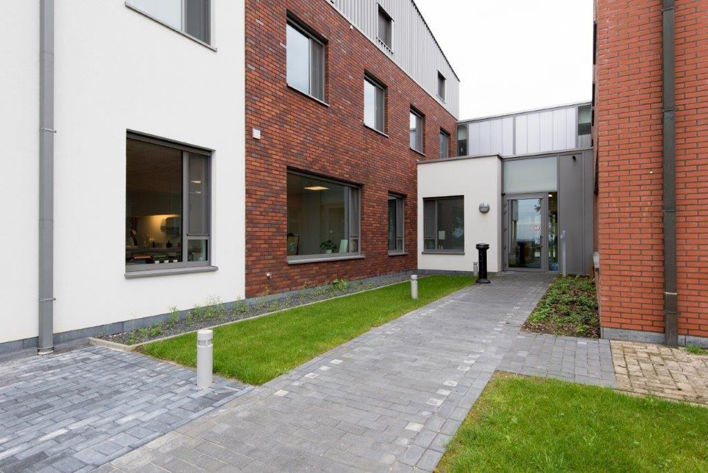 Het transparante inkomvolume verbindt de nieuwbouw met het bestaande gedeelte. (Beeld: VK Architects & Engineers)