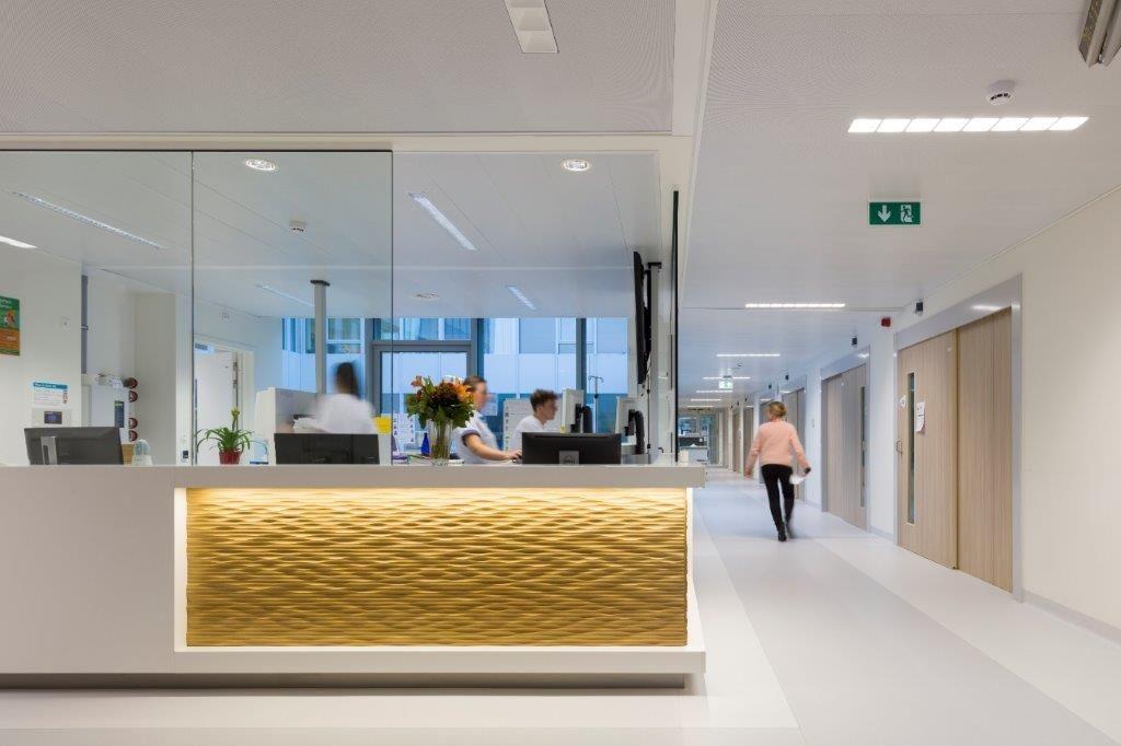 De lichtgrijze loper, geïntegreerd in de witte pvc-vloer, creëert meer afstand tot de kamers, waardoor de patiënt minder gestoord wordt. (Beeld: Ruimtesinbeeld)