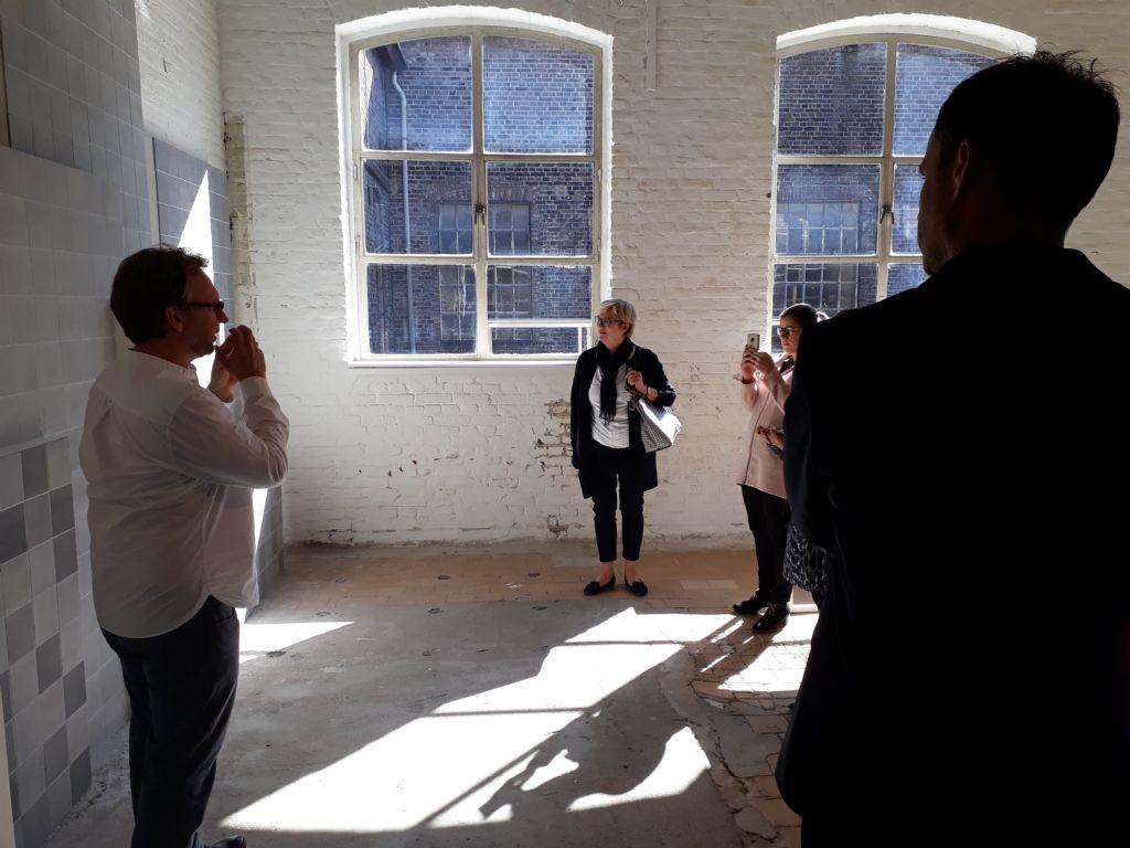 Des compositions de produits actuels sont présentées dans plusieurs salles de l'usine, où les murs d'origine révèlent des carreaux d'époque.