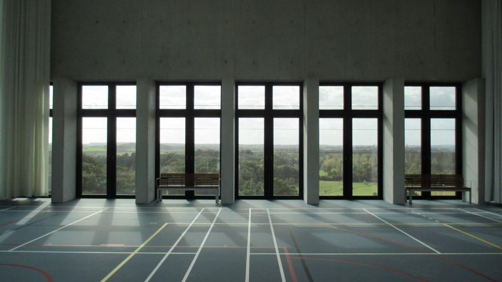 De 450 m² grote sporthal op de bovenste verdieping van de Therapietoren biedt een panoramisch uitzicht op de groene omgeving ten oosten van Leuven.