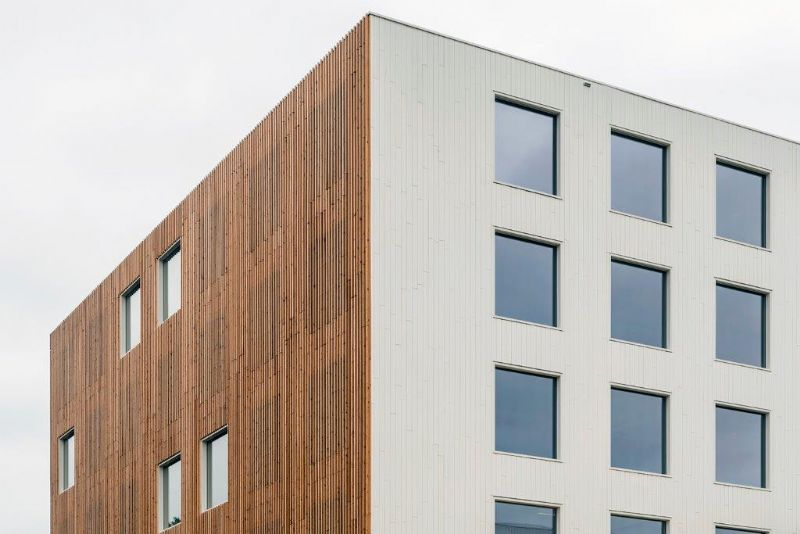 De volledige omtrek van het complex is bekleed met een houten schil. Op de gevels die zich richten naar de omgeving behoudt de beplanking zijn natuurlijke kleur, op de twee 'tussengevels' is ze wit geschilderd. (Foto: Marc Sourbron)