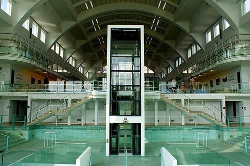 Het kleine bad op de derde verdieping, bereikbaar via een lift of trappen aan de zijde van de Place Xavier Neujean, vormt de nieuwe publieke toegang van het Cité Miroir-complex.